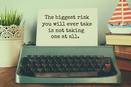 "vintage typewriter and paper with the printed text ""The biggest risk you will eve take, is not taking one at all"""